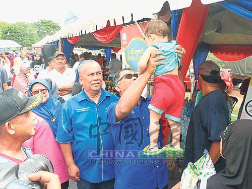 依德利斯哈侖(右)拜訪選民時,抱起一名小孩與小孩玩樂。
