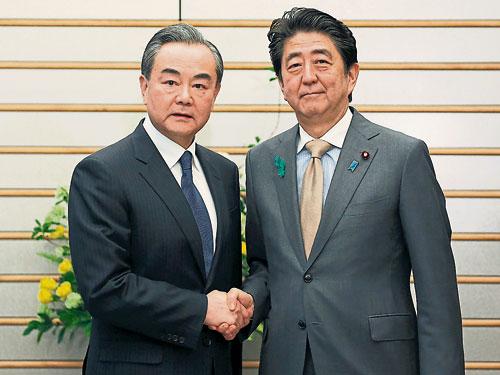 王毅(左)週一與日本首相安倍晉三會面。(歐新社)