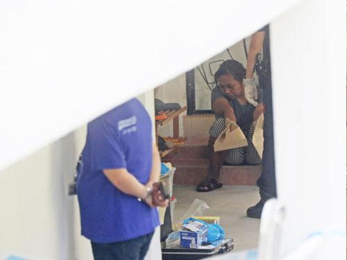案發後,被告坐在鄰居單位門口,等著被帶回警局問話。(檔案照)