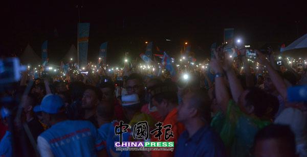 支持者亮起手機,形成一片燈海。