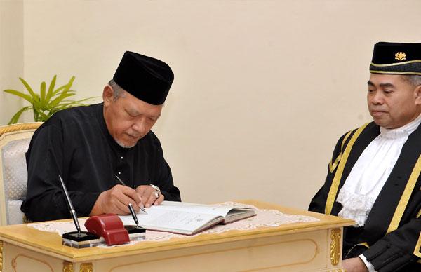 阿末耶谷(左)在阿末峇仄的見證下,簽署委任狀。