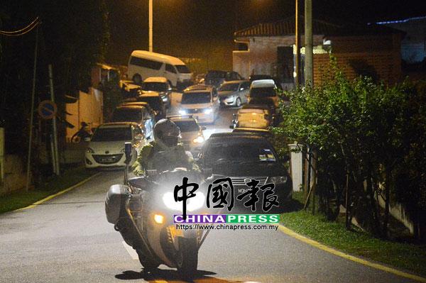 大型巡邏摩哆開路,休旅車和轎車從納吉住家駛出。