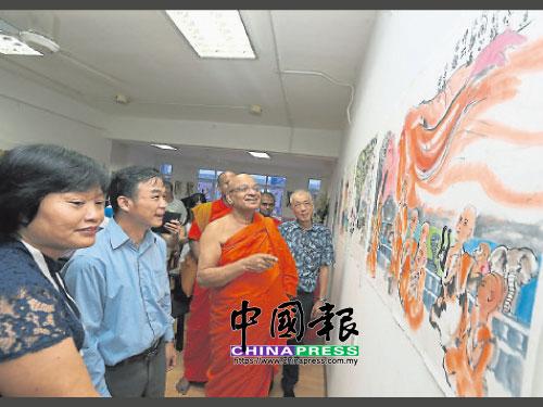 黃淑燕(左起)和鍾耀強向達摩拉達那長老講解《難得聞正法》畫作。
