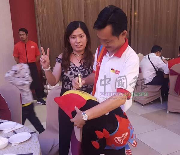 謝琪清應支持者的要求,在烏巴玩偶上簽名留念。