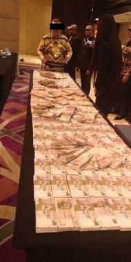 """""""大馬王子""""將最少100疊500港元鈔票鋪滿整張長桌。"""
