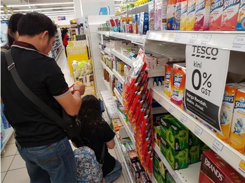 """特易購霸級市場內貼著""""零消費稅""""的告示,也有員工專門為客戶掃瞄商品的新價格。"""