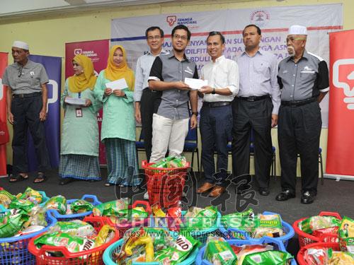 法米(前排左4)移交開齋禮品給受惠者;左3為國能企業組主任拿督威拉羅斯蘭阿都拉曼。