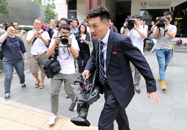 朝鮮一名記者周日抵達濱海灣的媒體採訪中心,被記者同業包圍。(歐新社)