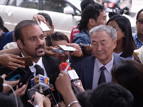 蓝卡巴星(左)陪同沙里布报案后,受各报记者围访。