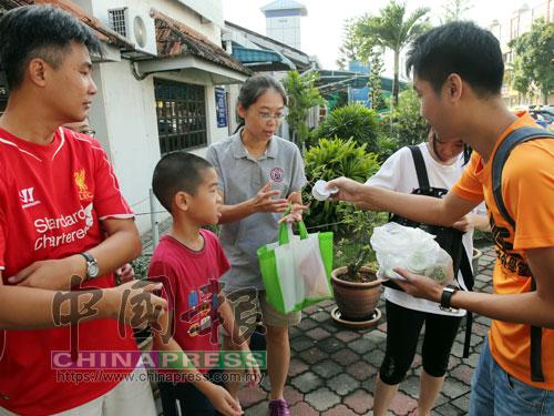 導纜員派發環保胸章予遊客,表揚他們的文明旅遊之舉。