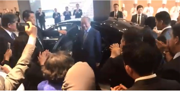 馬哈迪(中)在一片掌聲中上車離開酒店。