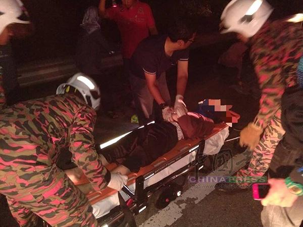 2名消拯員準備將一名傷者抬上救護車。