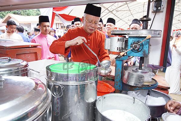 納吉親自為民眾盛煎堆甜品。