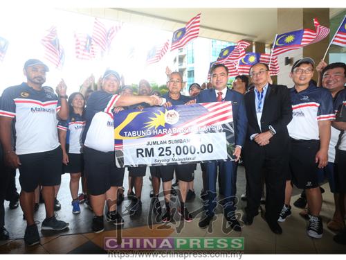陸兆福(前排右3)從大馬保時捷車隊籌委會主席拿督鍾鎮強(左2)手中,接過2萬5000令吉的大馬希望基金支票。