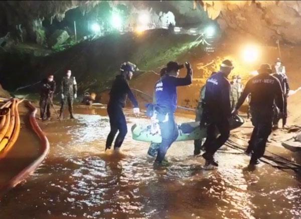 一名少年周二正由潛水員和救援隊抬出洞口。(美聯社)