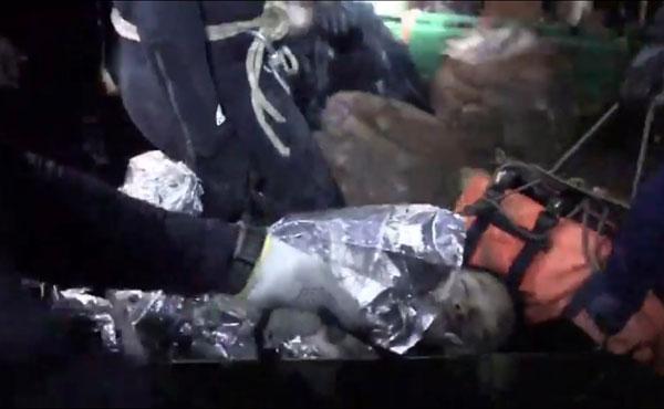 泰國當局公布的片段,顯示周二一名脫困少年,被保溫物料包裹著,他則處於昏睡中。(美聯社)