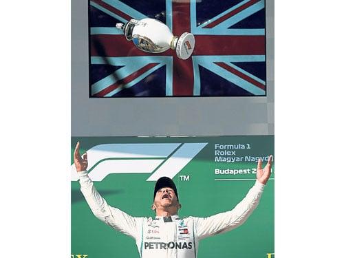 哈米頓興奮地拋起了在匈牙利站冠軍獎杯;這也是英國人本賽季第5個分站冠軍。(歐新社)
