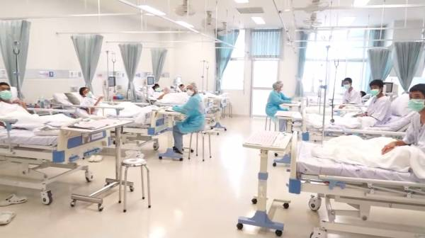 獲救少年在醫院接受治療,他們躺在床上戴著口罩,接受媒體拍照。(法新社)
