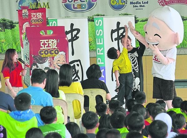 一年級的學生使出渾身力量跳高,與Ah Huat亞發公仔玩舉手擊掌。