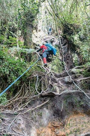 捉著繩子攀爬樹根,這段路驚心動魄。