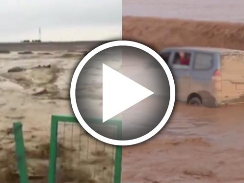影片顯示河水上漲,一輛私家車被困水中。