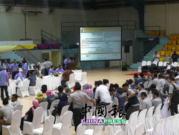 總計票中心正在宣佈各別投票站的成績,並把成績投影到螢光幕上。