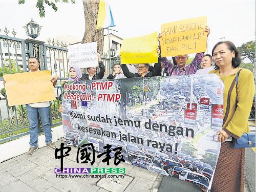 峇六拜自由工業區勞資雙方代表,週四早上在檳州議會大廈前高舉大字報,表達力挺檳州交通大藍圖的立場。