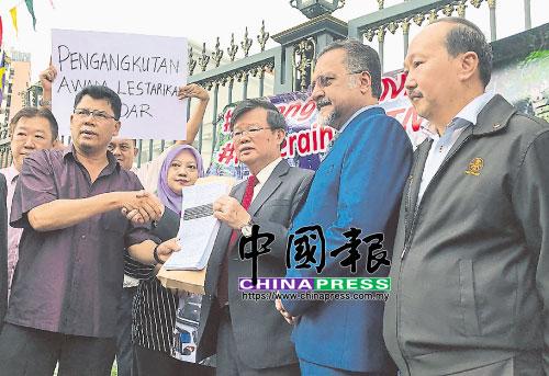纳沙鲁丁(左起)移交支持槟州交通大蓝图联署支持信给曹观友后,两人握手为礼;右起为王竞庆、槟州地方政府委员会主席佳日星等人。
