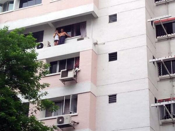阿叔和養女無法從門口逃出,爬出窗外站在窗沿等候救援。