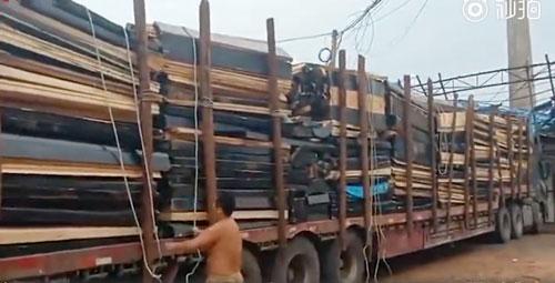 畫面顯示,一輛卡車上載滿了棺材板。