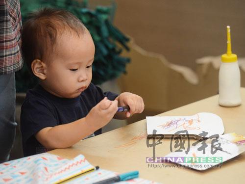 小朋友在紙皮上繪畫。