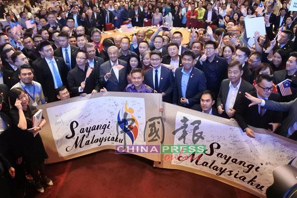 全體出席晚宴的旅居中國大馬人,與馬哈迪一同揮動大馬國旗。