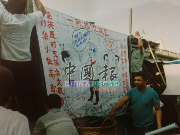 當時的民主行動黨舉行示威,大罵教育部長安華和甲首長拿督拉欣,並以一幅巨型漫畫的布幔前自編自導自演,引起群眾圍睹。