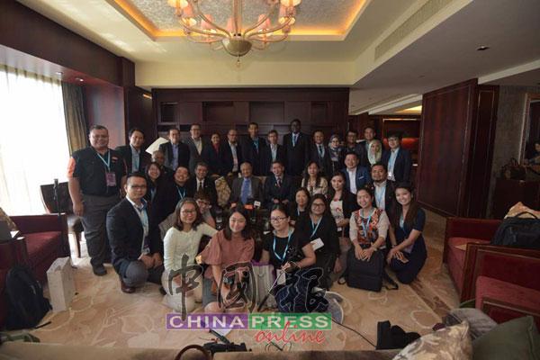 馬哈迪(坐者中)及內閣部長在記者會結束后,與隨團訪華的馬來西亞記者合照,為訪華行劃上句點。