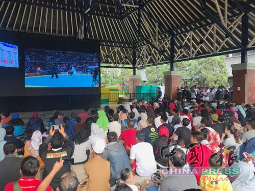 沒有門票怎辦?在賽館外看直播!東道主印尼在首次列為亞運項目的馬來武術16個項目中勇奪14金。多個公斤級別的搏擊項目都打入決賽,引起印尼民眾的熱捧,比賽門票也早早售罄,但當局在賽館外的小禮堂準備了大螢幕直播,現場氣氛熱鬧,好比一個小賽館。(攝影梁展威)