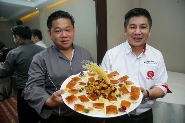 何志強師傅(右)和何順文師傅手中捧著的就是兩人大力推薦之作─鵝肝慕斯片皮乳豬。