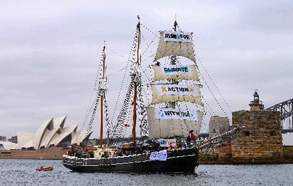 """""""350澳洲""""周六出動掛起抗議標語牌的帆船,穿越悉尼港。(路透社)"""