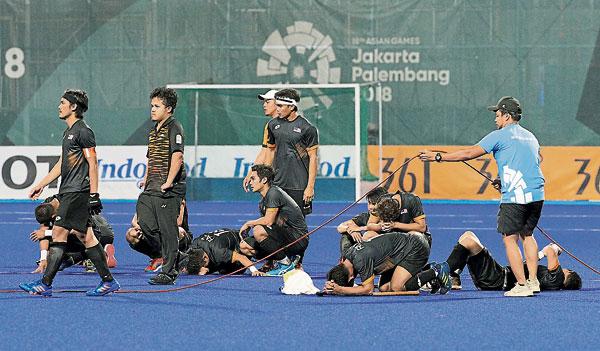 馬來西亞隊把握不住大好形勢,結果金牌夢碎,沮喪不已。(美聯社)