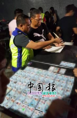 莫哈末凱佔副警監(左)正檢查該夜店的營業執照。