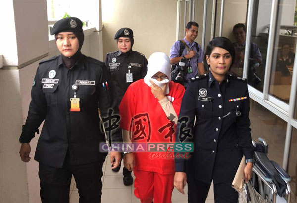 女被告西蒂諾芭希雅(前排左2)在警方帶領下,前往芙蓉推事庭面控,全程以手帕遮臉,以免面目曝光。