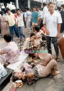 數名大難不死的在場者,被救出後,坐在現場外休息,同時等候隨行家人的消息。
