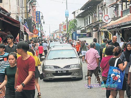 人潮眾多,不少遊客被迫行走在街道上,與車輛並肩而行,險象環生。