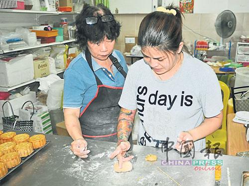 鄔碧雲(左)應顧客所求,教授製作月餅。