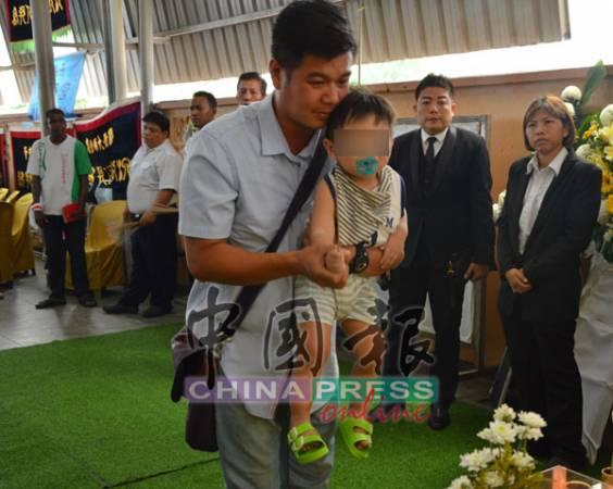 廖信翔抱著兒子,在妻子靈堂前拈香,送她最后一程。