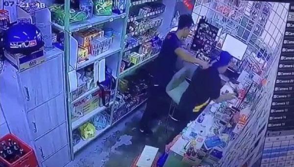 其中一名刀匪闖入迷你市場后,以刀挾持男店員。