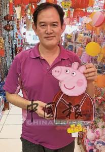 賀文生展示一款以粉紅豬小妹造型設計的傳統玻璃紙燈籠。