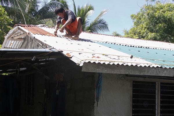 居民用粗繩加固屋頂,防強風摧毀。(法新社)