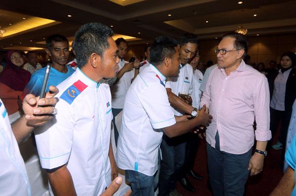 安华(右)到场时,受到党员欢迎。