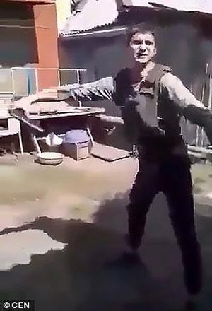穿着防弹衣的多莫维伊,手中拿着枪对准自己的腹部。