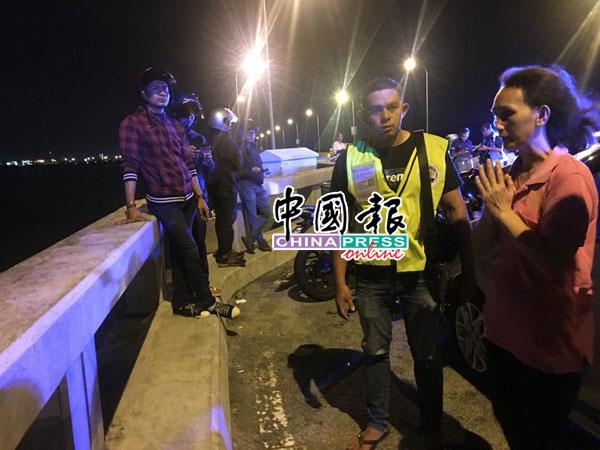 坠海女子母亲(右)双手合十诵经,希望搜救人员找到女儿,女儿能平安。